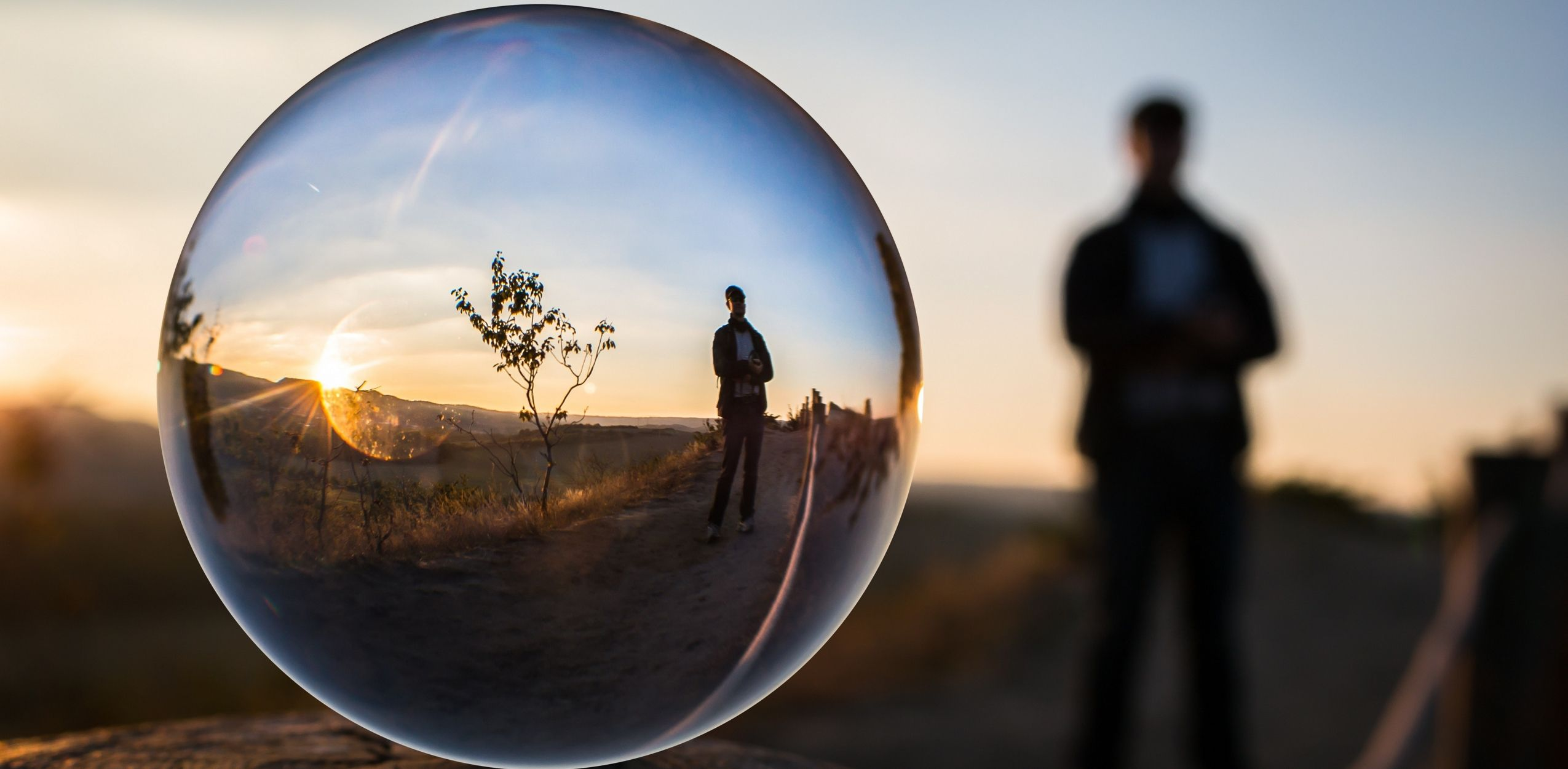 A sunset horizon and a person standing fairly close by, all reflected through a bubble up-close.